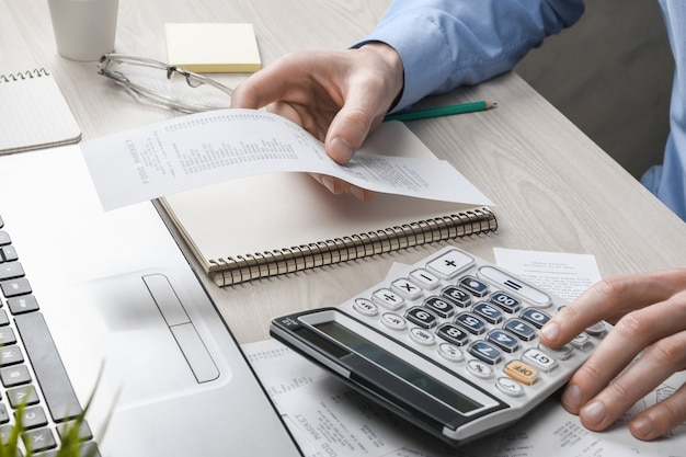 Man hand using calculator and writing make note with calculate about cost and taxes at home office. businessman doing some paperwork in the workplace