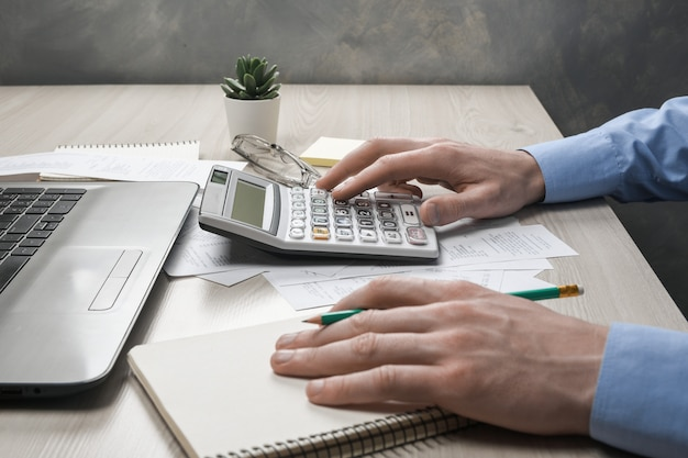 Man hand using calculator and writing make note with calculate about cost and taxes at home office.