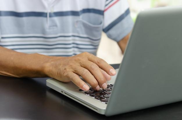 Рука человека, используя портативный компьютер на столе у себя дома, поиск информации в интернете в интернете, работа из дома. бизнес-концепция