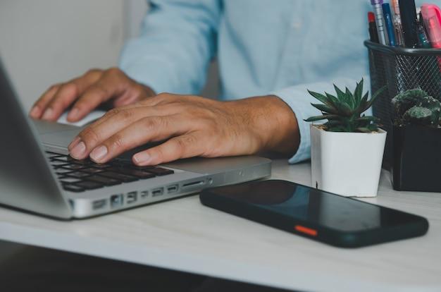 Рука человека с помощью клавиатуры компьютера портативного компьютера. поиск в интернете, информации, социальных сетях. предприятия, торгующие онлайн-покупками.