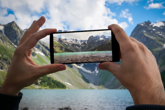 Рука человека с помощью фото мобильного телефона. горная природа