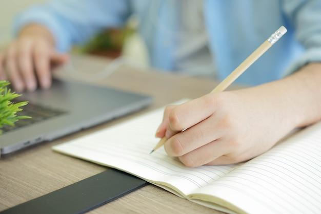 새로운 정상적인 라이프 스타일 개념을 배우기위한 숙제 또는 연습 시험을 작성하는 연필을 사용하는 사람 손