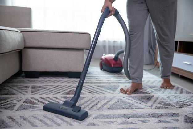 Man hand vacuuming carpet at home