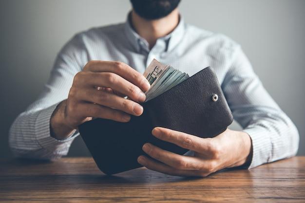 Бумажник руки человека с деньгами на столе