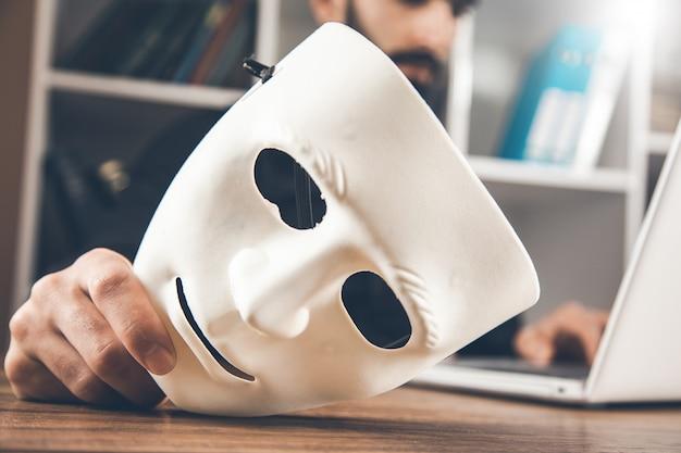 机の上のコンピューターで男の手の白いマスク