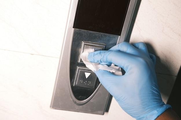 엘리베이터 버튼 아래로 닦는 남자 손