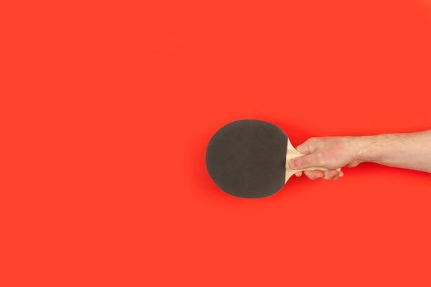 赤の上に黒の卓球パドルを持つ男の手