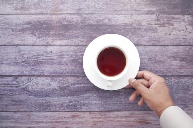 Рука человека с чашкой зеленого чая на столе