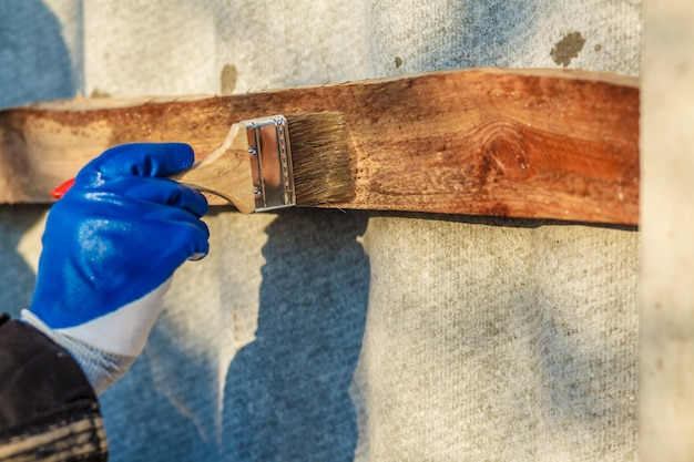 A man hand with blue glove holding paint brush applying wood lacquer