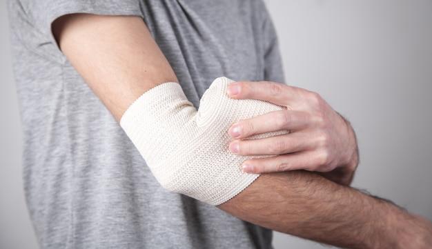 Man hand with elastic bandage on elbow.