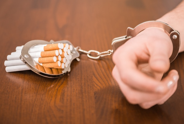 Man hand with handcuffs and cigarettes on the table.
