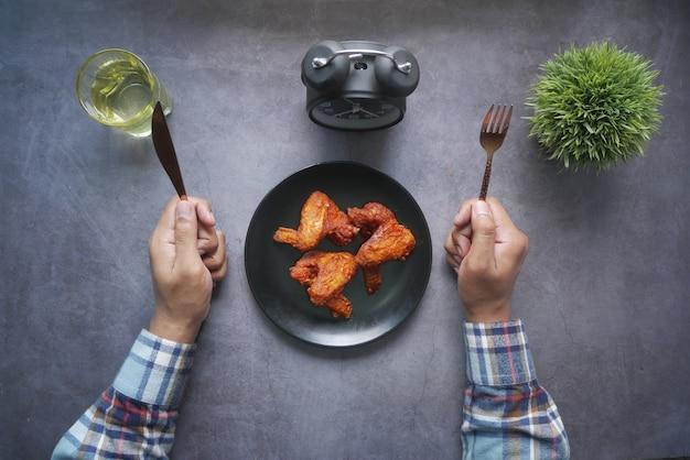 나이프와 포크는 접시에 프라이드 치킨 필레를 먹고 기다리고 남자 손