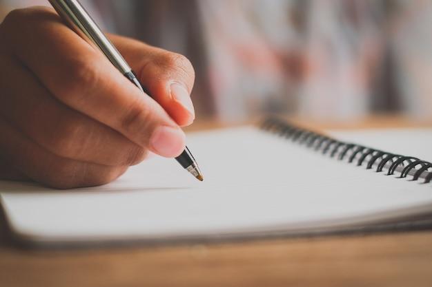 ノートにペンを書いている男の手。ペンで手をつないでください。机の上の白、自然からの木の模様、本を書いています。