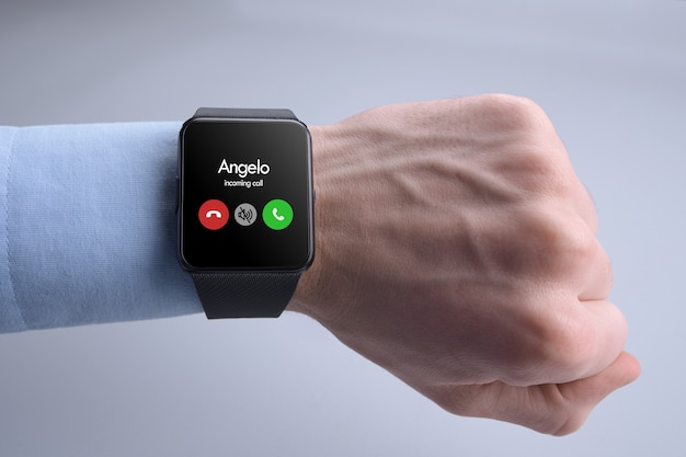 電話を受けるかどうかを検討しているスマートウォッチの着信通話を持っている人の手。