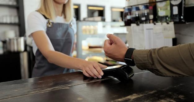 支払い、非現金取引、側面図に端末を使用してスマートウォッチを持った男の手。非現金支払いの概念。黒の背景のテーブルのpos-terminal。