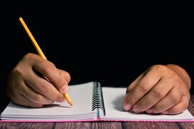 Рука человека с желтым карандашом, писать на ноутбуке.