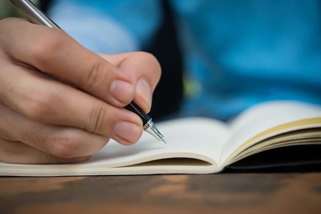Scrittura manuale dell'uomo sul taccuino.