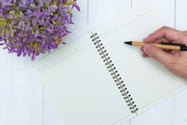Man hand writing on blank page of notebook paper with pen, office supplies, top view.
