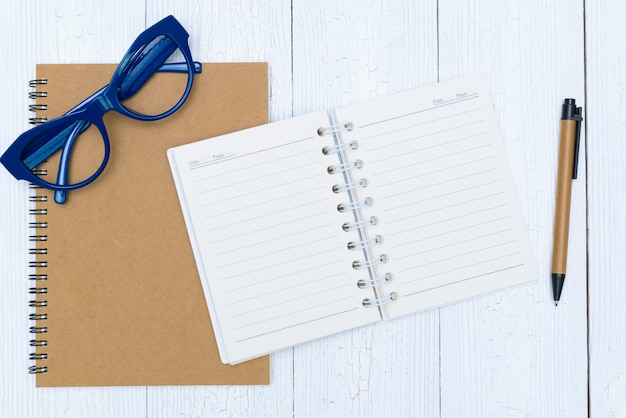 Man hand writing on blank page of notebook paper with pen