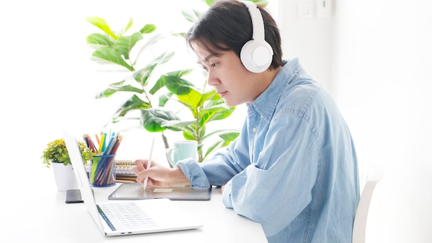 Man hand writing on digital tablet with white headphones on and plants in the background