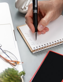 Man hand writing in note book on a grey office desk near laptop and cell phone close up