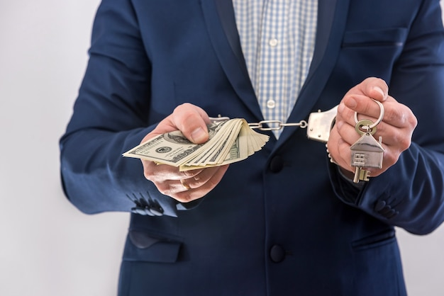 Man in handcuffs holding dollar banknotes isolated, close up