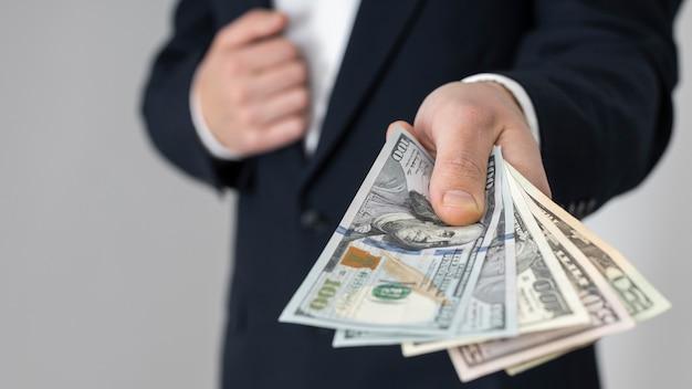 달러 지폐의 무리를 전달하는 남자