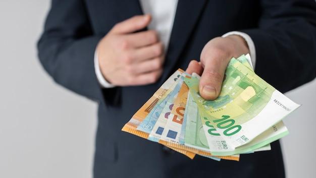Мужчина вручает кучу банкнот евро