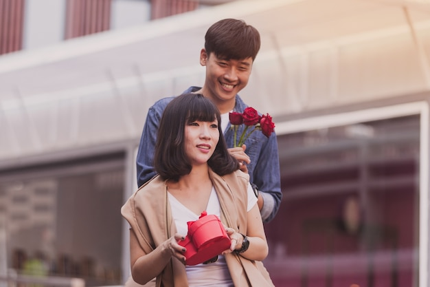 Man handing a gift and roses to a woman