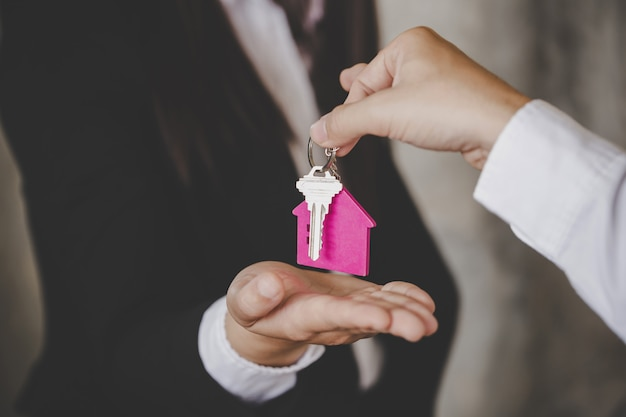 Man handing over the house keys to a new home inside empty gray colored room.