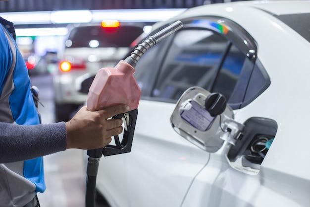 男はガソリンスタンドで車のタンクのガソリン燃料ノズルをポンプ処理します。