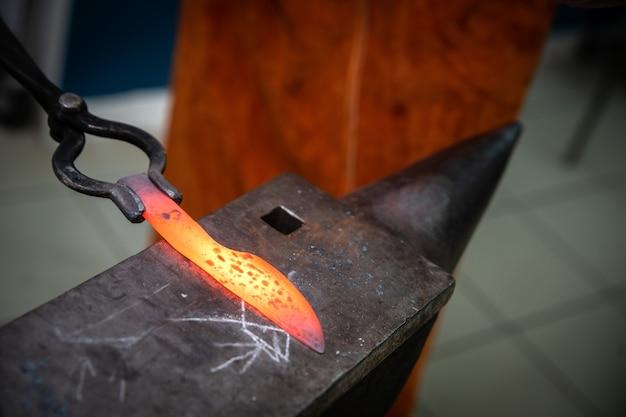 Мужские руки изготавливают стальной нож