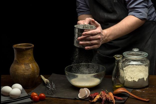 남자 손은 반죽을 준비하기 위해 유리 그릇에 밀가루를 붓고 있습니다.