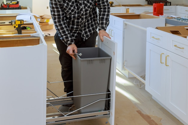 Man hands assembling furniture garbage bin in the kitchen