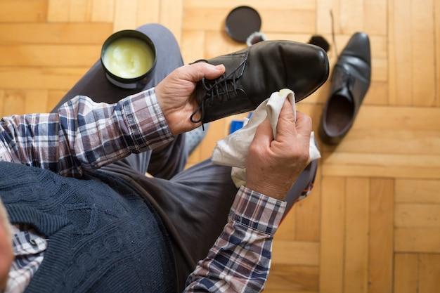 Руки человека чистят обувь тряпкой и воском для обуви для улучшения состояния обуви, полировки обуви