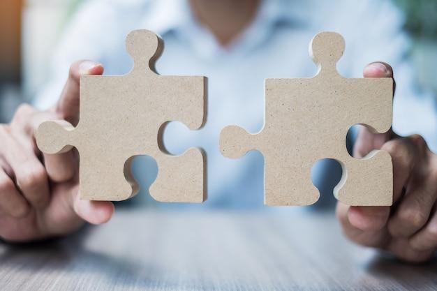 テーブルの上のカップルのパズルを接続する男の手、オフィス内の木製のジグソーパズルを保持しているビジネスマン。ビジネスソリューション、使命、目標、成功、目標、戦略の概念