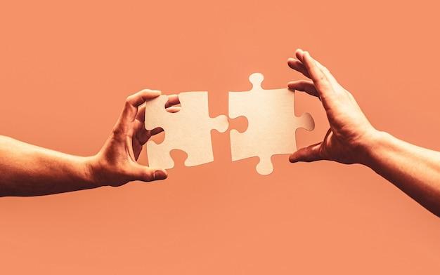 カップルのパズルのピースを接続する男の手。ビジネスソリューション、ターゲット、成功、目標、および戦略の概念。ジグソーパズルを接続する手。ビジネスソリューション、成功と戦略の概念。