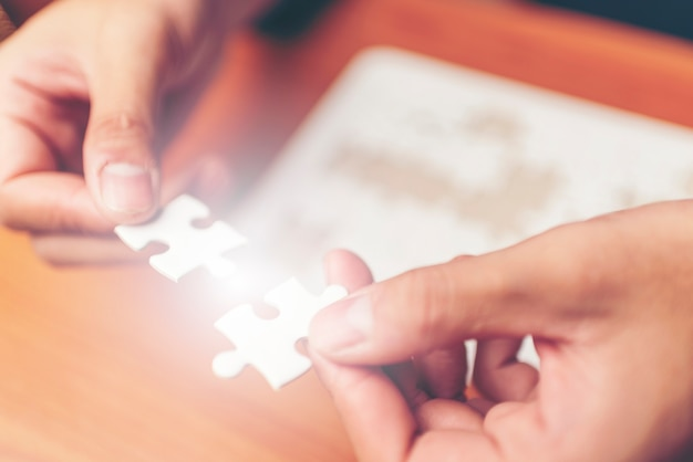 Man hands connecting couple puzzle piece in office. business solutions, target, successful