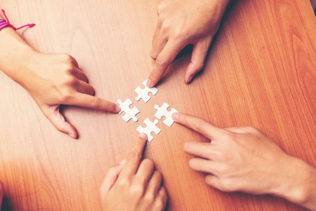 Man hands connecting couple puzzle piece in office. business successful