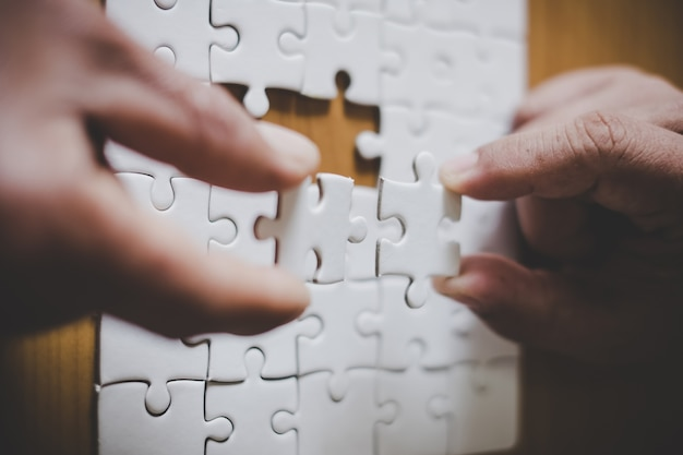 Man hands connecting couple puzzle piece in office.