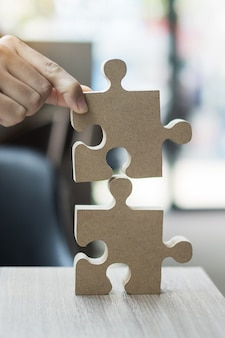 Man hands connecting couple puzzle over table, businessman holding wood jigsaw inside office.