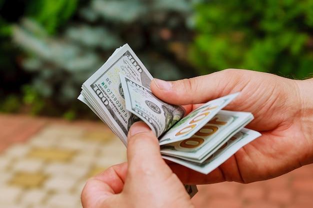 Человек руки, считая долларовые банкноты. считаю или тратьте деньги.