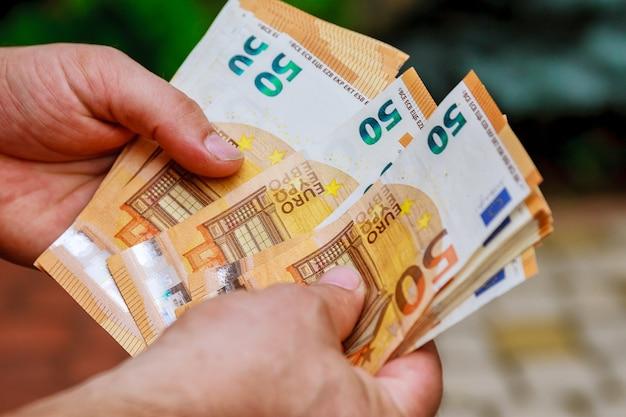 Человек руки считает банкноты евро нас. считать или потратить деньги.