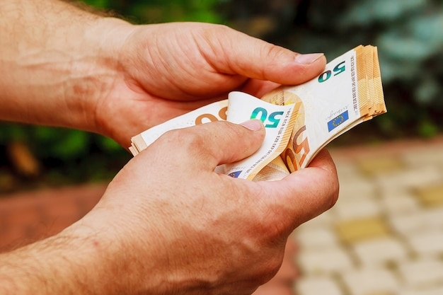 Руки человека, считая банкноты евро нас.