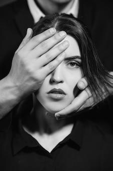 Руки человека, закрывающие лицо женщины. концепция подавления управления. узник непреодолимых отношений или брака