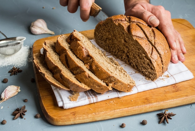 Man hands cut with knife piece of rye bread