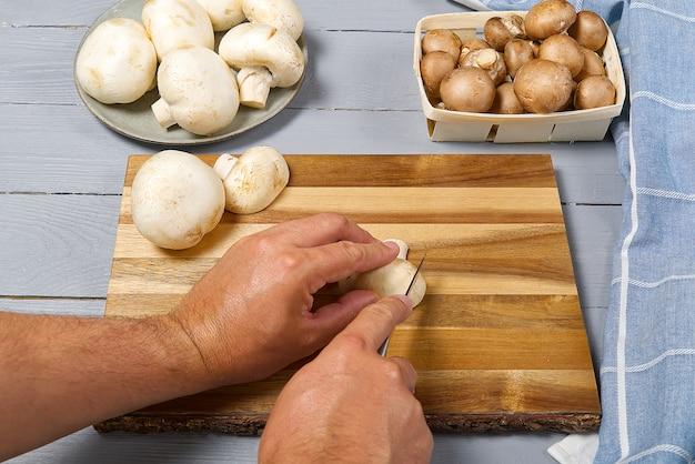 男の手が新鮮なシャンピニオンキノコをカッティング。灰色の木製のテーブルに白と茶色のシャンピニオンスライスシャンピニオン。