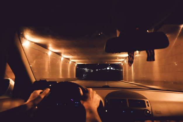 男は車のダッシュボードと夜の街の背景を持つ現代の車のハンドルにドライバーを手渡します