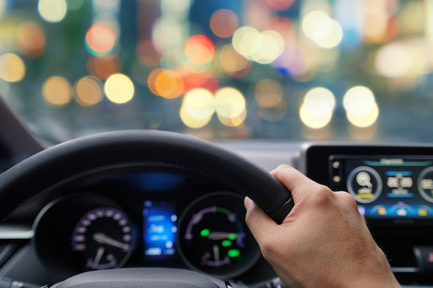 Man hands driver on steering wheel of a modern car