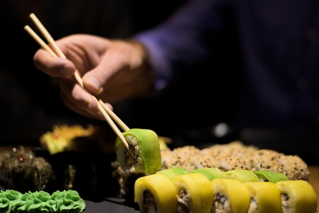 Man hands eating sushi rolls with wooden sticks